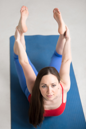 dhanurasana: Beautiful happy young woman in bright colorful sportswear working out indoors on blue mat. Girl doing Dhanurasana, Bow Pose. Full length. Top view. Vertical image