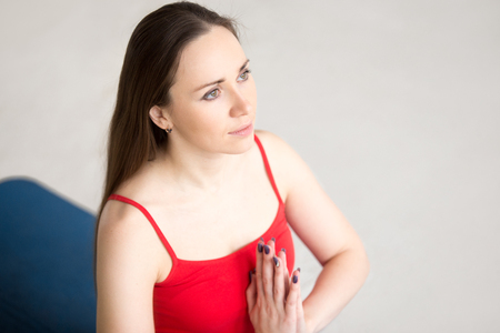 Portrait of beautiful young woman in bright red tank top. Attractive model sitting on meditation session in Prayer position indoors. Copy space