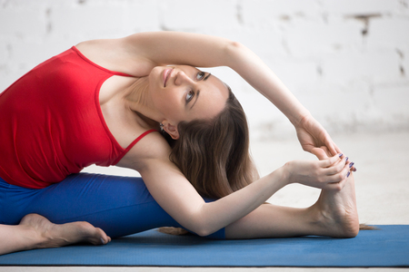 janu: Portrait of beautiful smiling young woman in bright colorful sportswear working out indoors. Girl sitting in Parivrtta Janu Sirsasana, Revolved Head-to-Knee Forward Bend posture on blue mat. Close-up