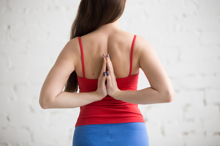 anjali: Beautiful young woman in bright colorful sportswear working out indoors in loft interior. Girl holding Anjali Mudra behind the back, exercise for flexible wrists, arms, shoulders. Close-up. Back view