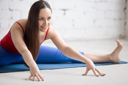 straddle: Beautiful happy young woman in bright colorful sportswear working out indoors on blue mat. Girl sitting in Wide-Angle Seated Forward Bend pose, Upavishtha Konasana, dragonfly yin posture. Close-up