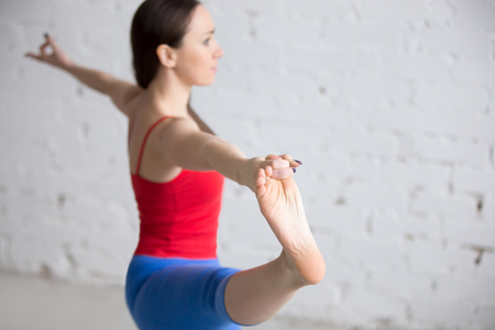 hasta: Beautiful young woman in bright colorful sportswear working out indoors in loft interior. Girl standing in Utthita Hasta Padangustasana posture. Close-up. Focus on foot. Copy space Stock Photo