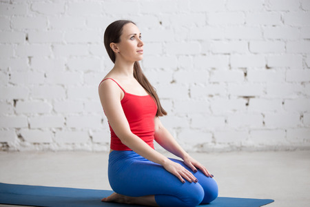 Portrait of beautiful young woman in bright colorful sportswear working out indoors in loft interior. Girl sitting in seiza, vajrasana, thunderbolt or diamond pose on blue mat. Full length