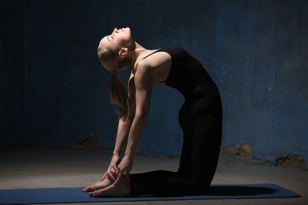 ushtrasana: Beautiful sporty fit young woman working out indoors against grunge dark blue wall. Model standing on her knees, doing backbend exercise Ustrasana, Camel Posture. Full length