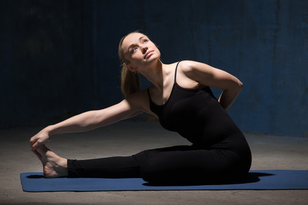 padma: Beautiful sporty fit young woman working out indoors against urban dark blue wall. Model sitting in Ardha Baddha Padma Paschimottanasana, Half Bound Lotus Forward Bend posture. Full length