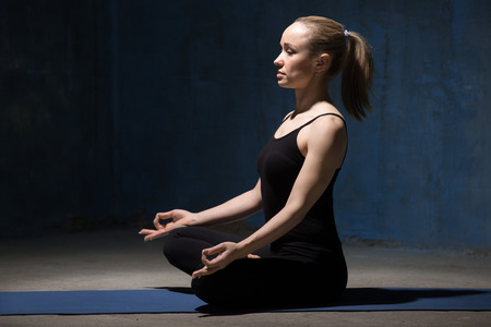 ardha: Beautiful sporty fit young woman working out indoors against urban dark blue wall. Model sitting on meditation session in Half Lotus Pose, Ardha Padmasana. Full length