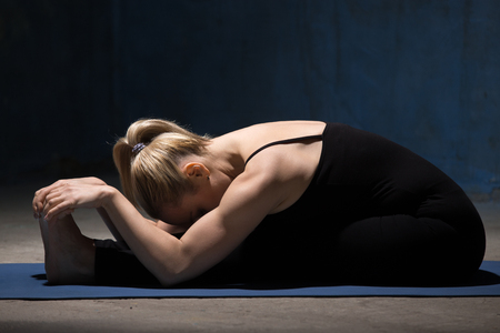 situp: Beautiful sporty fit young woman working out indoors against grunge dark blue wall. Model doing Seated Forward Bend yoga pose, Paschimothanasana (Caterpillar - yin posture). Full length