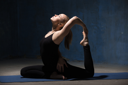 eka: Beautiful sporty fit young woman working out indoors against urban dark blue wall. Model sitting in variation of One Legged King Pigeon Posture (Eka Pada Rajakapotasana). Full length