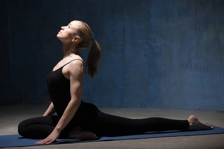 pose: Beautiful sporty fit young woman working out indoors against grunge dark blue wall. Model doing easy variation of One Legged King Pigeon Pose (Single Pigeon), Eka Pada Radjakapotasana. Full length