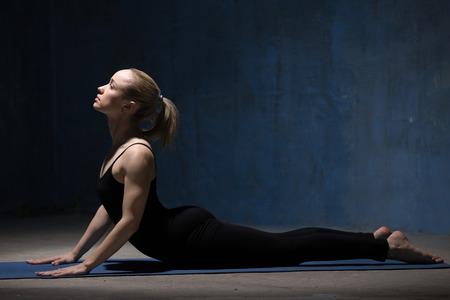 bhujangasana: Beautiful sporty fit young woman in black sportswear working out indoors against grunge dark blue wall. Model doing cobra asana, bhudjangasana (Seal - yin yoga variation). Full length. Copy space