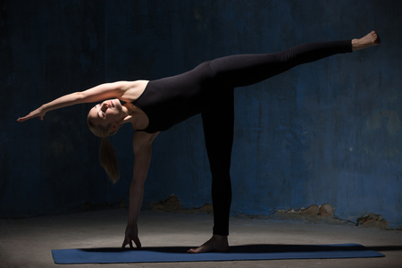 chandrasana: Portrait of attractive cool sporty young woman in black sportswear working out indoors against grunge dark blue wall. Model standing in Ardha Chandrasana posture, Half Moon Pose. Full length