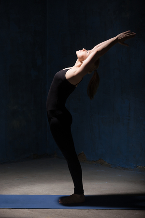 ardha: Beautiful sporty fit young woman in black sportswear working out indoors against grunge dark blue wall. Model doing Ardha Chakrasana, Standing Backward Bend Pose. Full length
