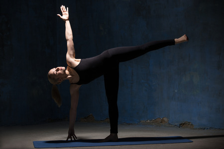 chandrasana: Beautiful sporty fit young woman in black sportswear working out indoors against grunge dark blue wall. Model standing in Ardha Chandrasana posture, Half Moon Pose. Full length. Stock Photo