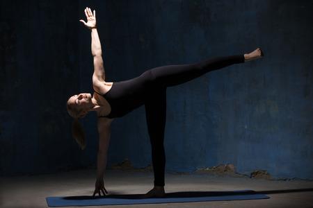 Bella sportivo in forma giovane donna in nero sportswear di lavoro al chiuso contro grunge parete blu scuro. Modello in piedi in Ardha Chandrasana postura, Half Moon Pose. Lunghezza intera.