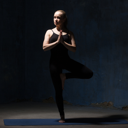 vriksasana: Beautiful sporty young woman in black sportswear working out indoors against grunge dark blue wall. Model doing Vrksasana Posture, Tree Pose. Square image. Full length