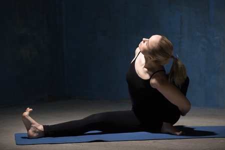janu: Beautiful sporty fit young woman working out indoors against grunge dark blue wall. Model sitting in variation of Parivrtta Janu Sirsasana or Baddha Ardha Samakonasana Pose. Full length. Copy space