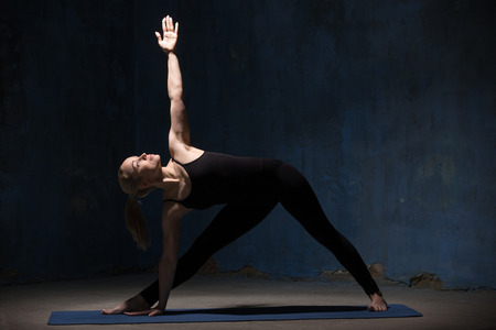utthita: Beautiful sporty fit young woman in black sportswear working out indoors against grunge dark blue wall. Model standing in Utthita Trikonasana, Extended Triangle Pose. Full length