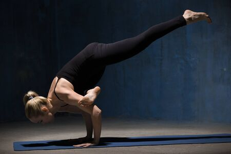 pada: Beautiful sporty fit young woman working out indoors against grunge dark blue wall. Model doing arm stand exercise, Eka Pada Galavasana, Flying Pigeon (Flying Crow) Pose. Full length Stock Photo