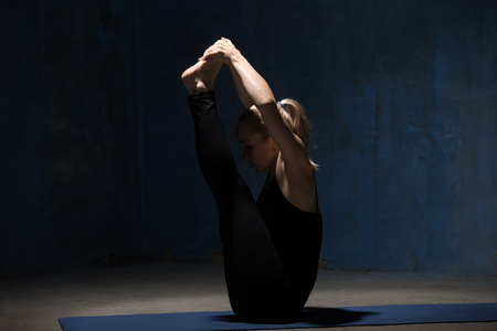 big toe: Beautiful sporty fit young woman in black sportswear working out indoors against grunge dark blue wall. Model sitting in Ubhaya Padangusthasana, Both Big Toe posture. Full length