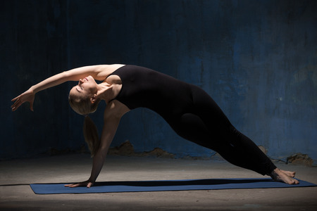 Portrait of beautiful sporty fit young woman in black sportswear working out indoors against grunge dark blue wall. Model doing Side Plank Posture, Pose of Vashista, Vasisthasana. Full length.