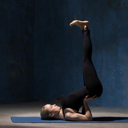 poses de modelos: Hermoso deportivo encaja mujer joven trabajando en el interior del grunge contra la pared azul oscuro. haciendo ejercicio de soporte del hombro, asana Viparita Karani modelo, al revés sello pose. Longitud total. imagen cuadrada Foto de archivo