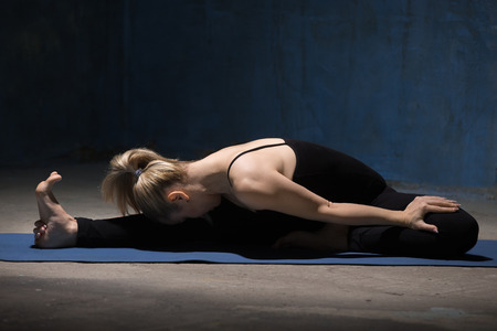janu: Beautiful sporty fit young woman working out indoors against grunge dark blue wall. Model sitting in variation of Janu Sirsasana or Head to Knee Forward Bend Pose. Full length Stock Photo