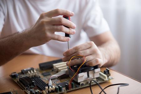 Close-up van de handen van de jonge computer ingenieur vaststelling van kapotte pc-onderdelen aan de balie in het kantoor aan huis