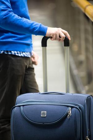 gente aeropuerto: Primer plano de las manos del hombre joven sosteniendo la maleta en la moderna terminal del aeropuerto. Viajar tío con ropa de estilo casual y elegante de pie con su equipaje mientras espera para el transporte. imagen vertical