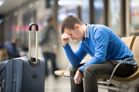 旅行: 交通機関を待っているカジュアルなスタイルの服を着ている若いハンサムな男の肖像画。モダンな駅の椅子にイライラした表情で座っているスーツケースと旅行疲