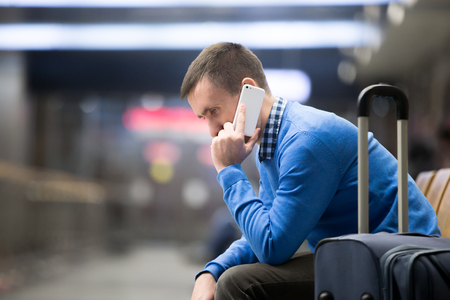 businessman waiting call: Portrait of young handsome guy wearing casual style clothes waiting for transport in modern station. Traveler making call using smartphone. Man travelling with suitcase sitting on a bench. Copy space