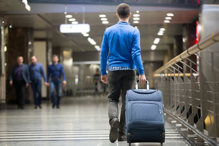 Young man pulling suitcase in modern airport terminal. Travelling guy wearing smart casual style clothes walking away with his luggage while waiting for transport. Rear view. Copy space