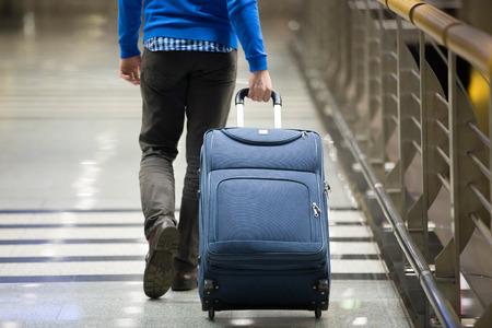 Jeune homme tirant une valise à terminal de l'aéroport moderne. guy Voyager porter des vêtements intelligents de style décontracté marchant loin avec ses bagages en attendant le transport. Vue arriere. Fermer Banque d'images - 54552656