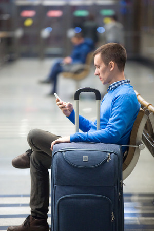 Portrait of young man sitting in airport terminal, holding cellphone. Traveler using public wifi, smartphone app, messaging. Male model travelling with suitcase, wearing blue casual style clothes