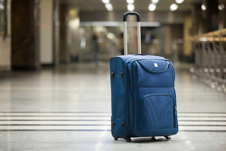 Large blue wheeled suitcase standing on the floor in modern airport terminal. Copy space Stockfoto