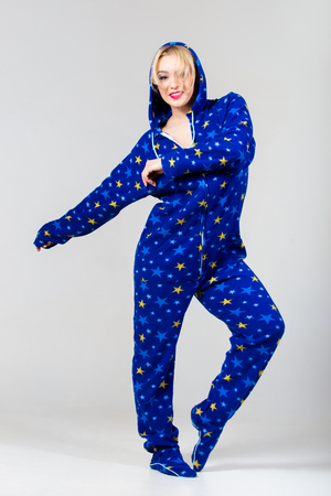 nightclothes: Smiling beautiful girl exercising in funny blue colored dungarees nightclothes with star pattern and a hood Stock Photo