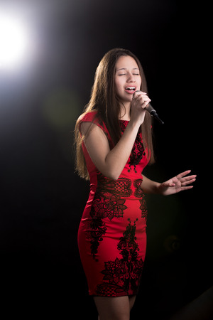 beautiful black woman: Portrait of beautiful girl in red dress standing in spotlight with microphone passionately singing with closed eyes Stock Photo