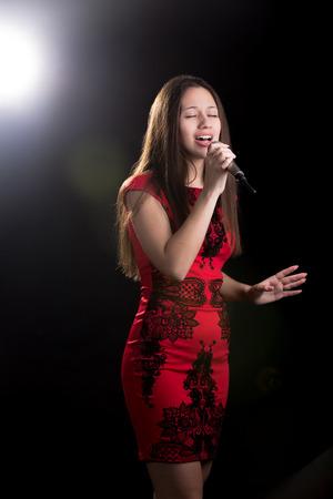 canto: Retrato de la hermosa ni�a de vestido rojo de pie en el centro de atenci�n con micr�fono con pasi�n cantando con los ojos cerrados Foto de archivo