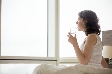 levantandose: Estilo de vida Retrato de una mujer joven sentada en la cama de agua potable después de levantarse. caucásica modelo femenino relajante en la mañana en su casa. Copyspace. Vista lateral