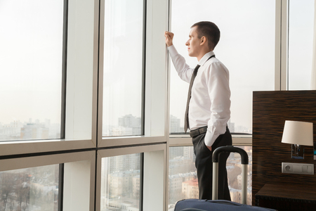 arrived: Young traveler businessman wearing white shirt and necktie standing in the hotel room with his luggage. Just arrived traveler looking in window at city scenery with thoughtful expression. Copy space