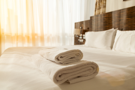 Stacked fresh white bath towels on the bed sheet. Close-up. Lens flair in sunlight