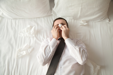 Portrait of young businessman wearing white shirt and necktie lying on the bed in the hotel room sick with flu. Caught cold and sneezing into tissue. View from above