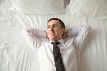 coming home: Young traveler businessman wearing white shirt and necktie lying on the bed in the hotel room with his hands behind head. Office worker relaxing after coming home with blissful expression