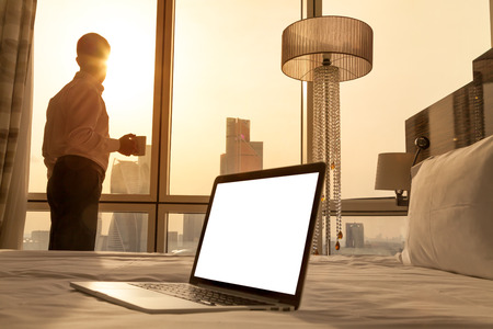 stay home work: Laptop computer on white bed sheets in cozy room with copy space blank screen. Young businessman with cup of coffee standing at window looking at city scenery on the background