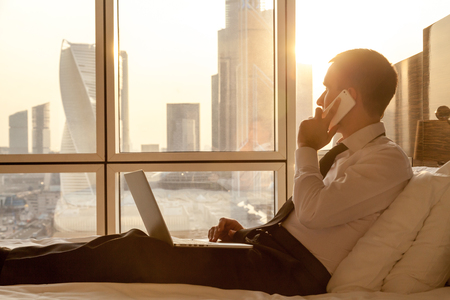 selfemployed: Handsome young businessman wearing formal white shirt and tie sitting on the bed with laptop in modern room. Self-employed person using smartphone and looking at sunny city view in window Stock Photo
