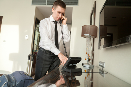 Young traveler businessman wearing white shirt and necktie making call after arriving in the hotel room with his luggage Imagens