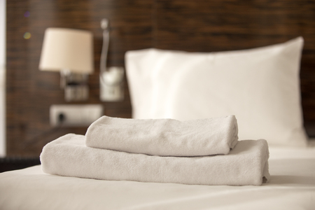 Stacked clean white bath towels on the bed sheets in hotel room, close-up Stock Photo