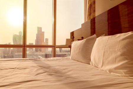 Bed maid-up with clean white pillows and bed sheets in empty room. Close-up. Lens flair in sunlight. Sunrise city view on the background