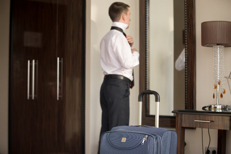 stay home work: Young traveler businessman wearing white shirt standing at the mirror and getting dressed for meeting or work after arriving in the hotel room with his luggage. Focus on the suitcase