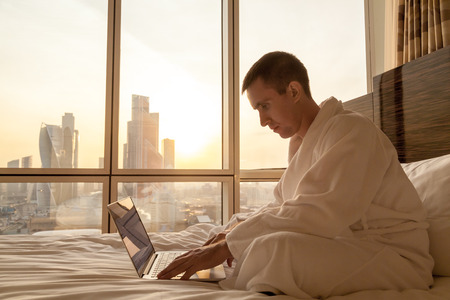 bath robe: Portrait of handsome young businessman wearing white bath robe sitting on the bed with laptop in modern room with sunset city view on background. Full length. Indoors. Copy space