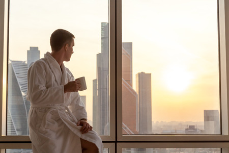 Focus on laptop computer with copy space blank screen on the bed. Young businessman sitting on window with cup of coffee looking at sunset city scenery Standard-Bild